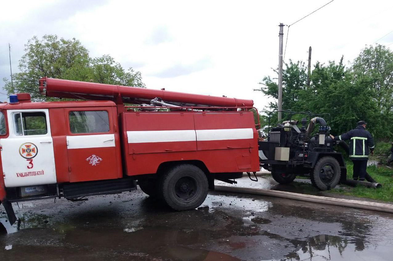 Пожежна машина відкачує воду із затопленного подвір'я
